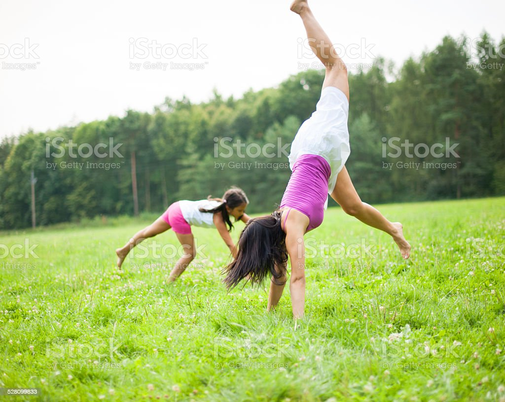 Mother and daughter cartwheeling in meadow stock photo