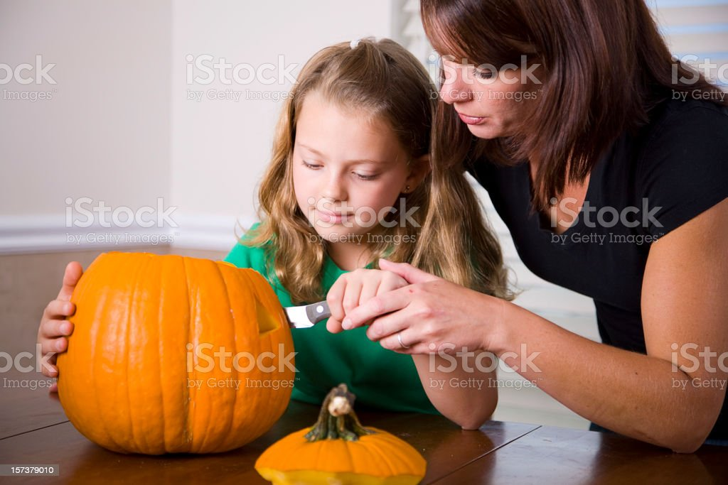 Mother and Daughter Carving a Pumpkin stock photo