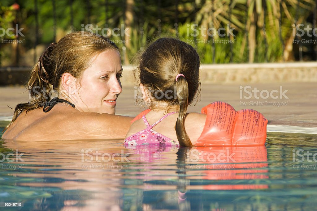Mother and daughter chat at edge of pool royalty-free stock photo