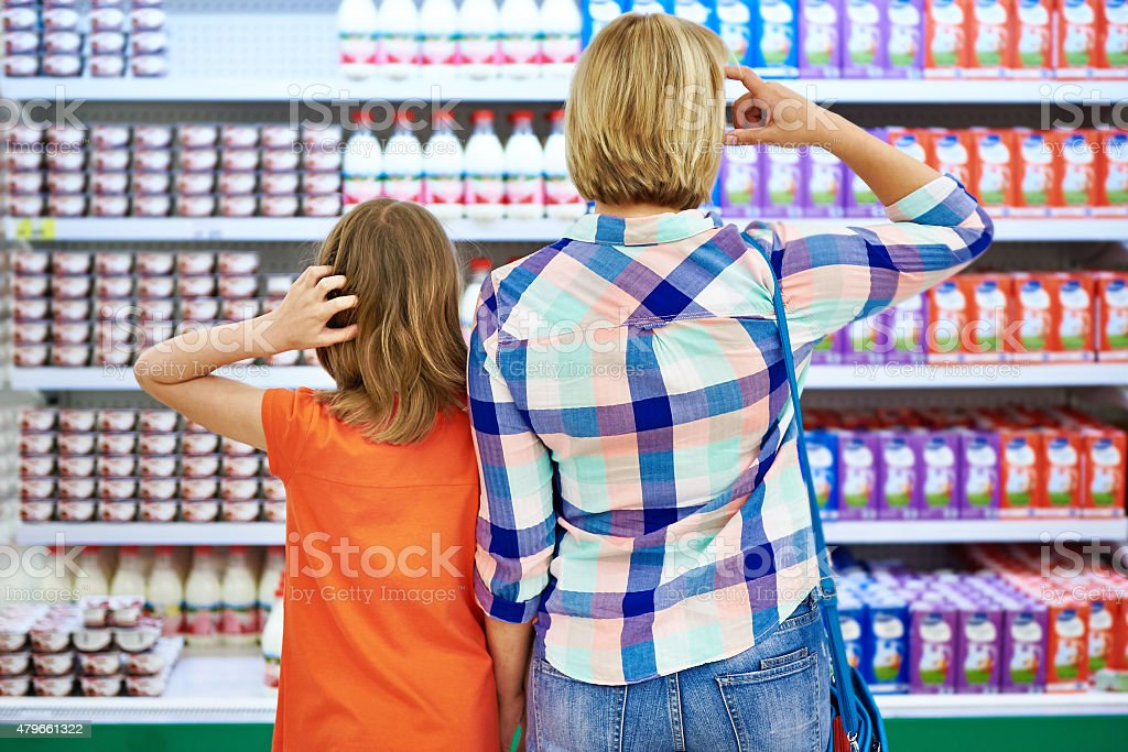 Mother and daughter choosing dairy products stock photo