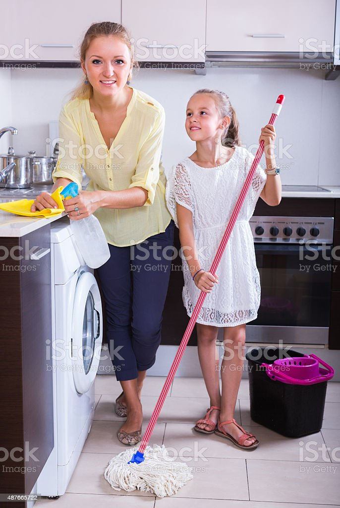 Mother and daughter cleanup at kitchen stock photo