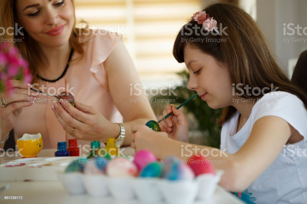 Mother and daughter coloring Easter eggs at home stock photo