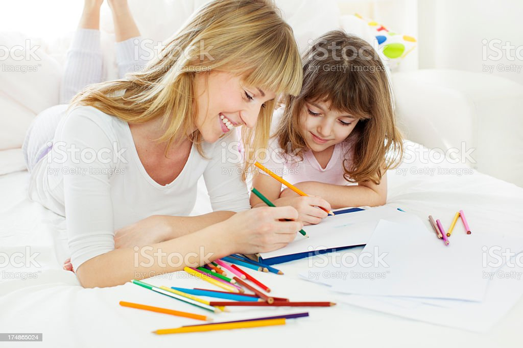 Mother and daughter coloring in bedroom. royalty-free stock photo