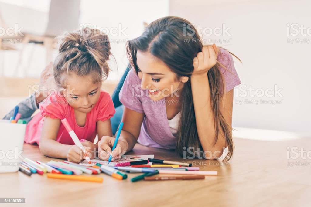 Mother and daughter coloring on the floor stock photo