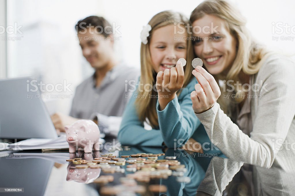 Mother and daughter comparing coins stock photo