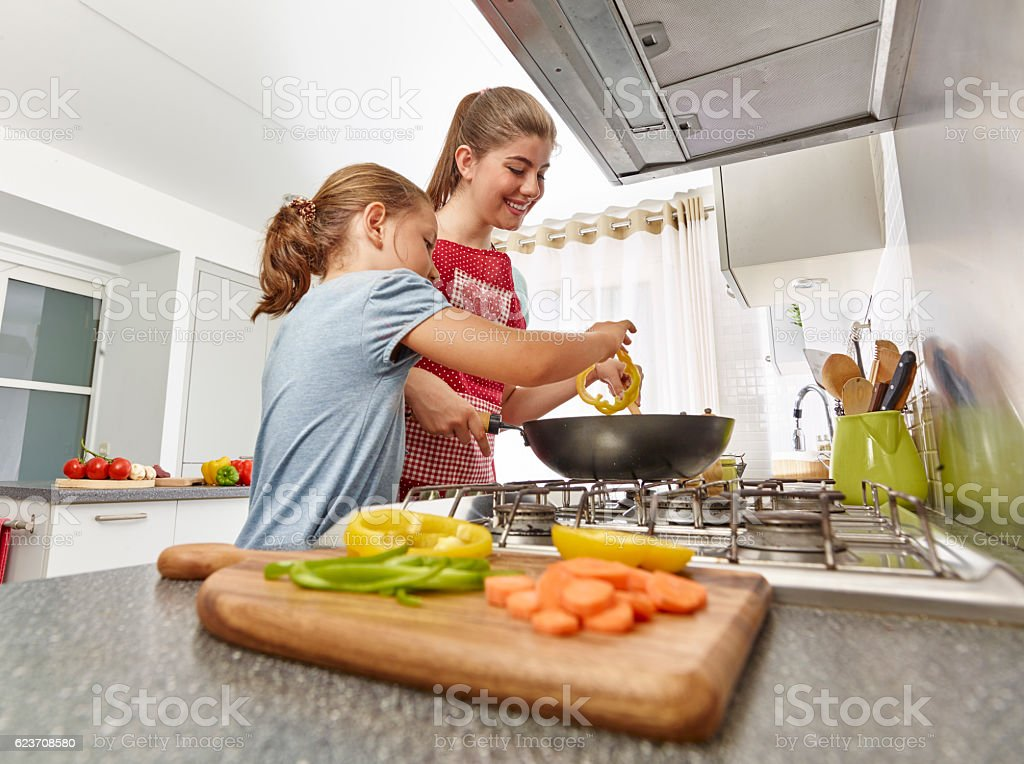 Mother and daughter cooking in kitchen stock photo