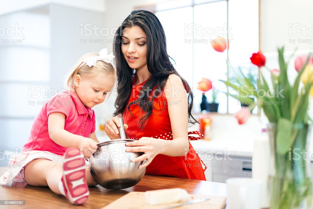 Mother and Daughter Cooking Together stock photo