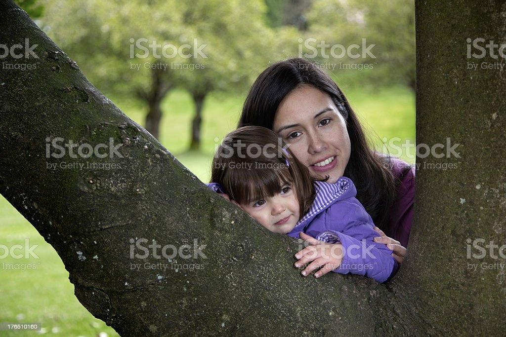 Mother and Daughter Cuddling as they Rest on a Tree royalty-free stock photo