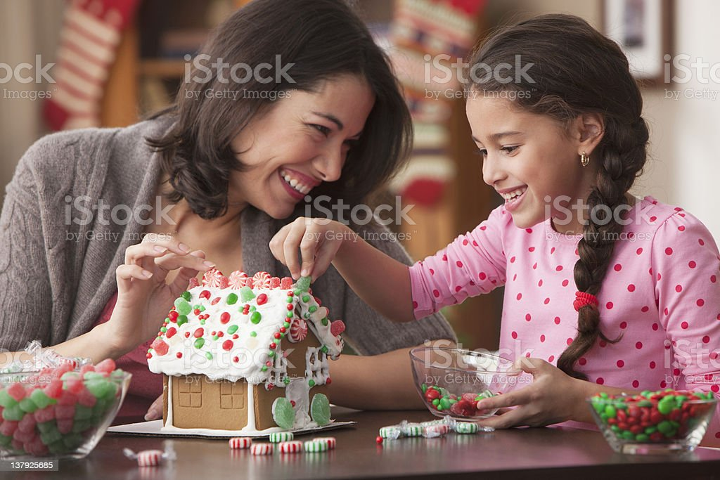 Mother and daughter decorating gingerbread house stock photo