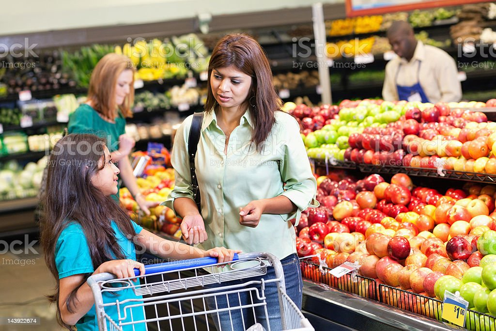 Mother and daughter discussing grocery purchases at the supermarket stock photo