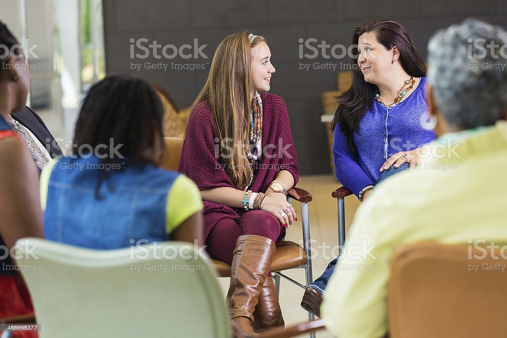 Mother and daughter discussing something during group meeting stock photo
