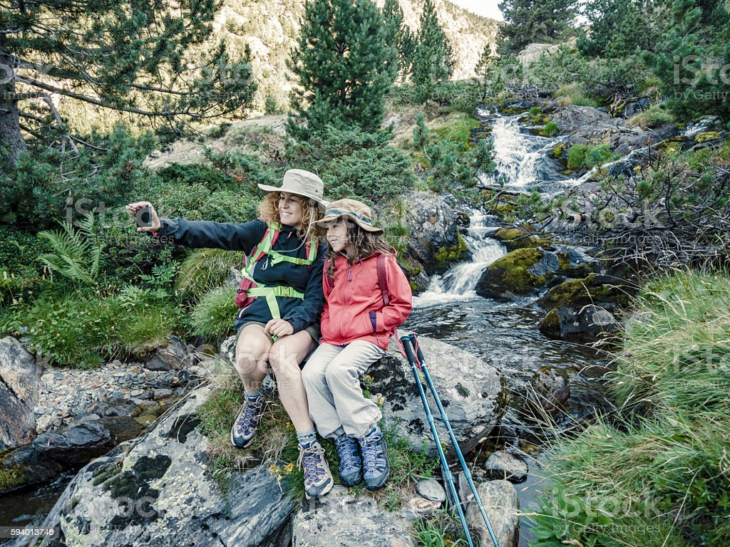 Mother and daughter doing a selfie in the mountains stock photo