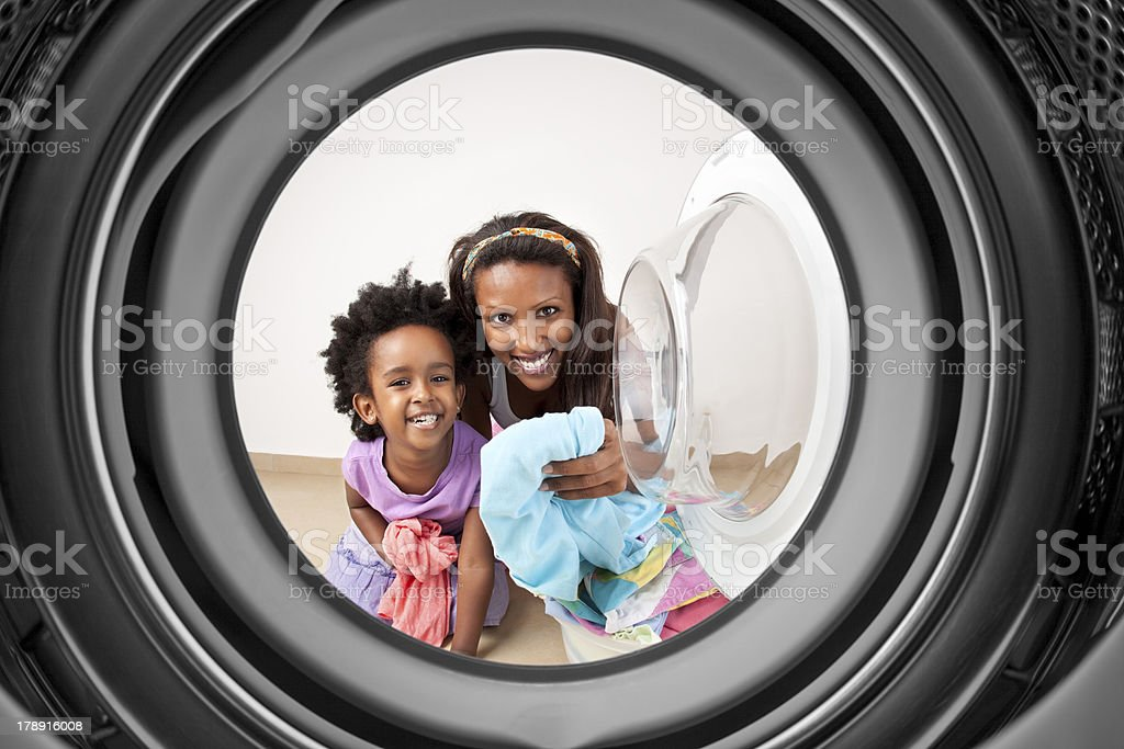 Mother and daughter doing laundry. stock photo