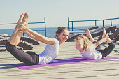 Mother and daughter doing yoga outdoors