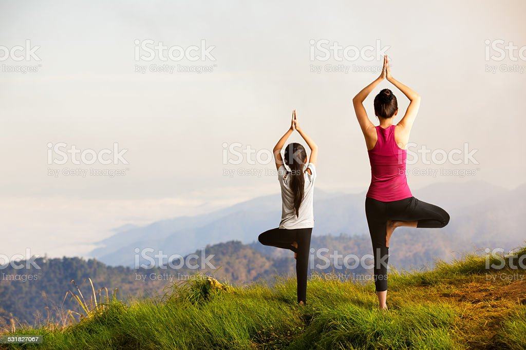 Mother and daughter doing yoga stock photo