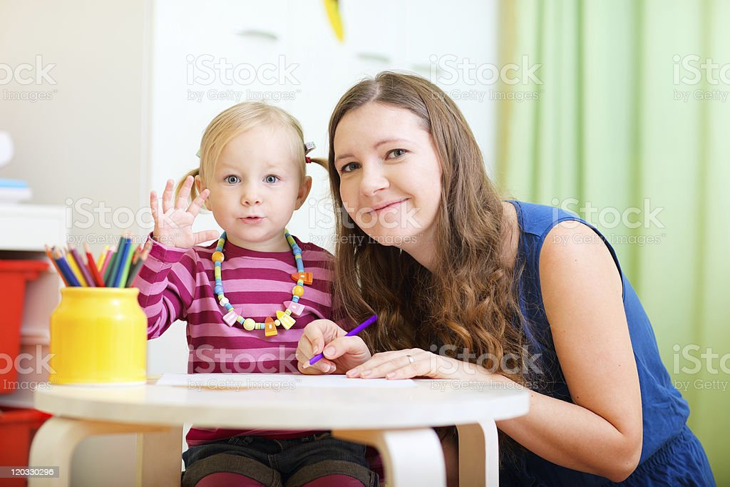 Mother and daughter drawing at a desk with colored pencils  royalty-free stock photo