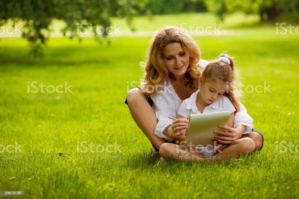 Mother and daughter drawing on grass in park royalty-free stock photo