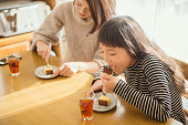Mother and daughter eat Castella together in room