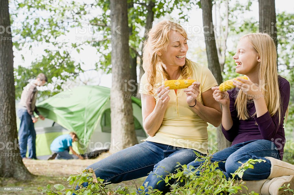 Mother and daughter eating corn together while camping in nature stock photo