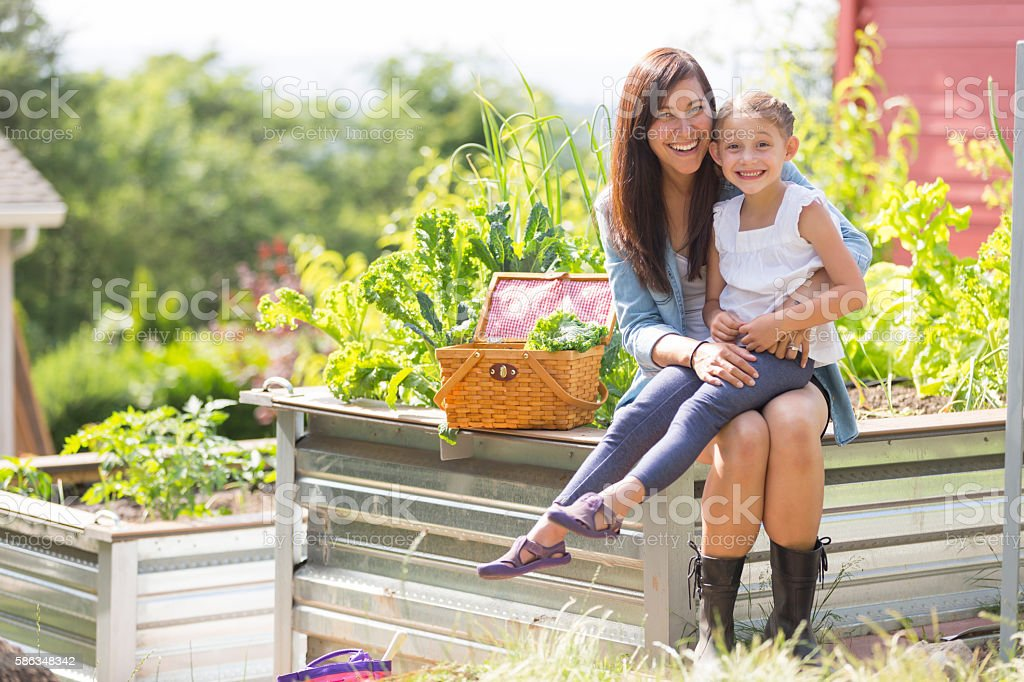 Mother and daughter enjoy gardening together outdoors stock photo