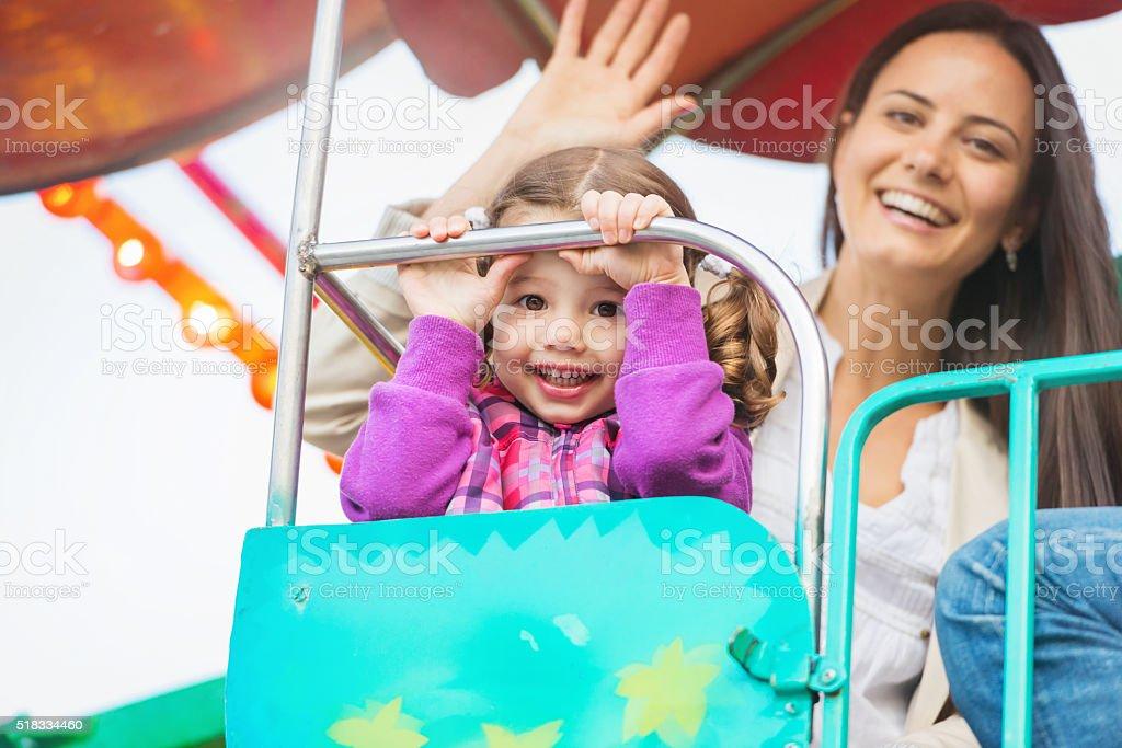 Mother and daughter enjoying fun fair ride, amusement park stock photo