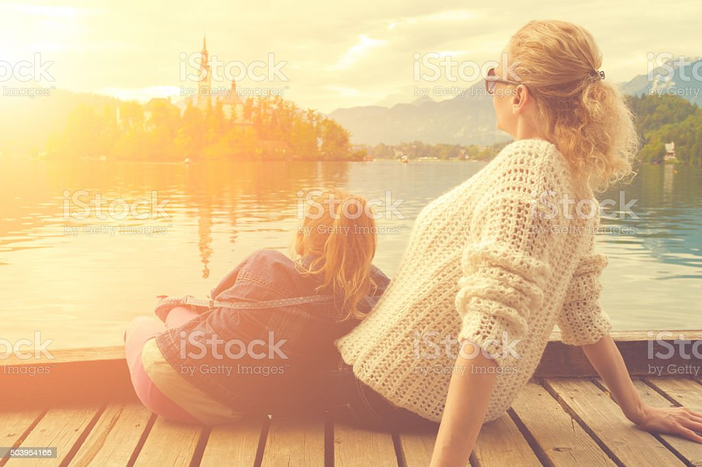 Mother and daughter enjoying sunset on a lake. stock photo