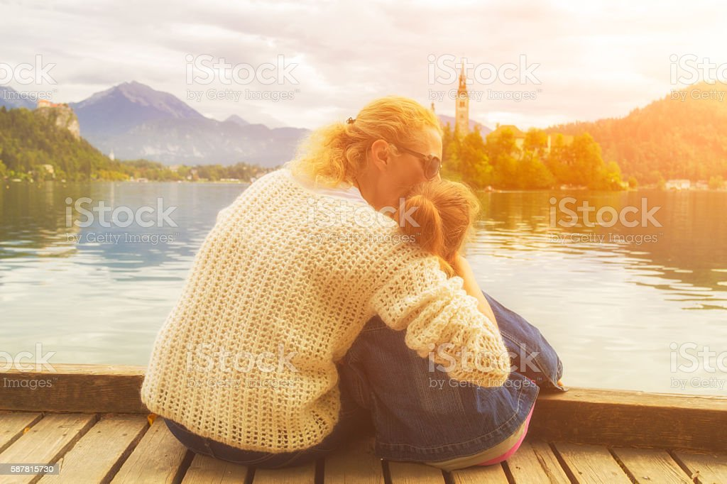Mother and daughter enjoying the view on a lake. stock photo