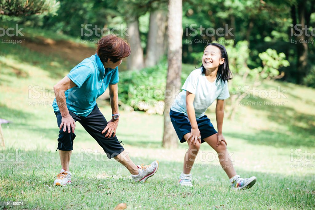 Mother and daughter exercising and stretching in Yoyogo Park, Japan stock photo