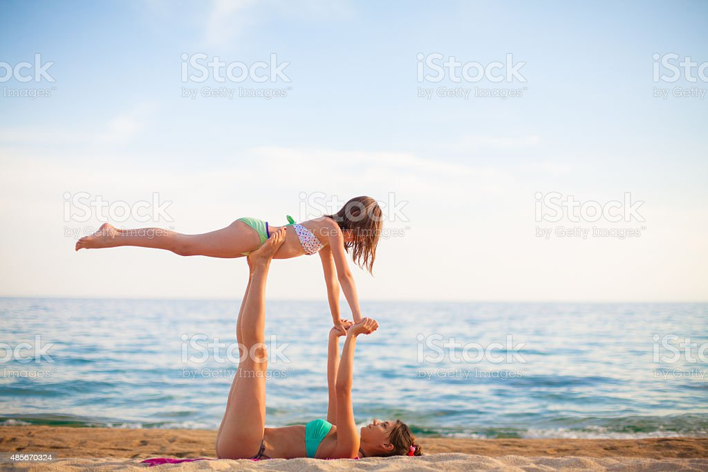Mother and daughter exercising on the beach stock photo