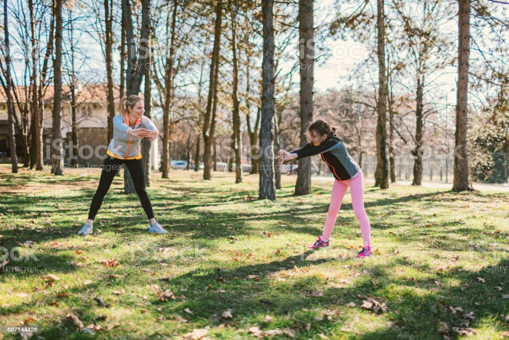 Mother and daughter exercising together stock photo