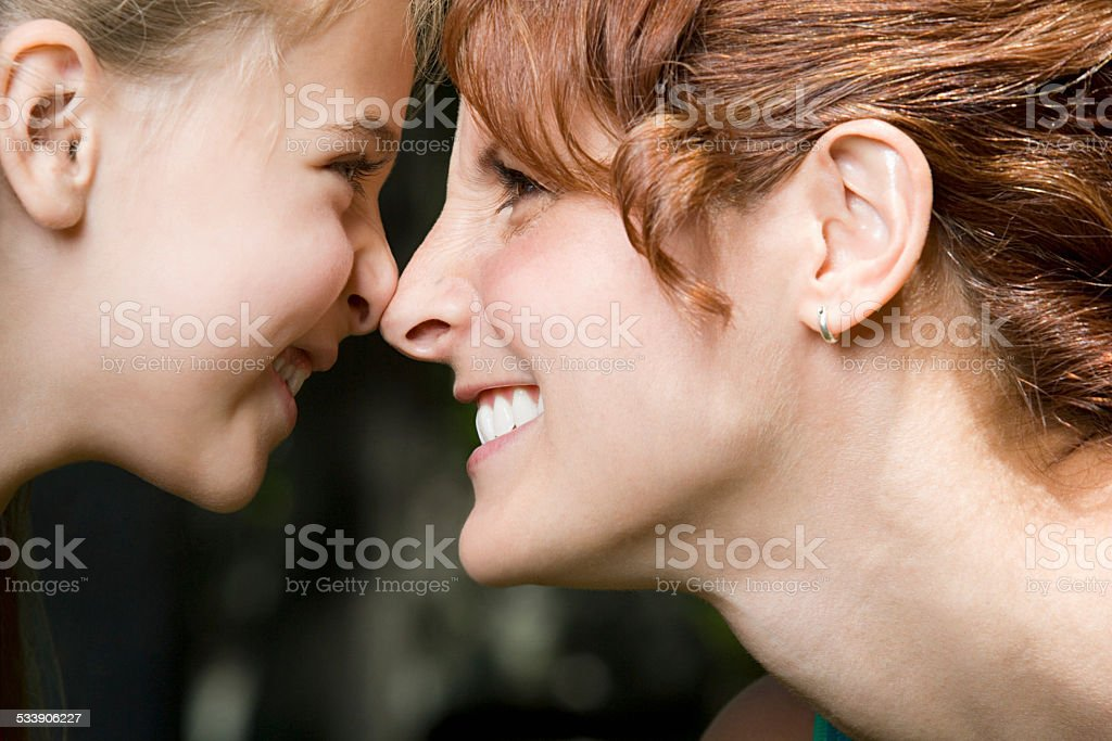 Mother and daughter face to face stock photo