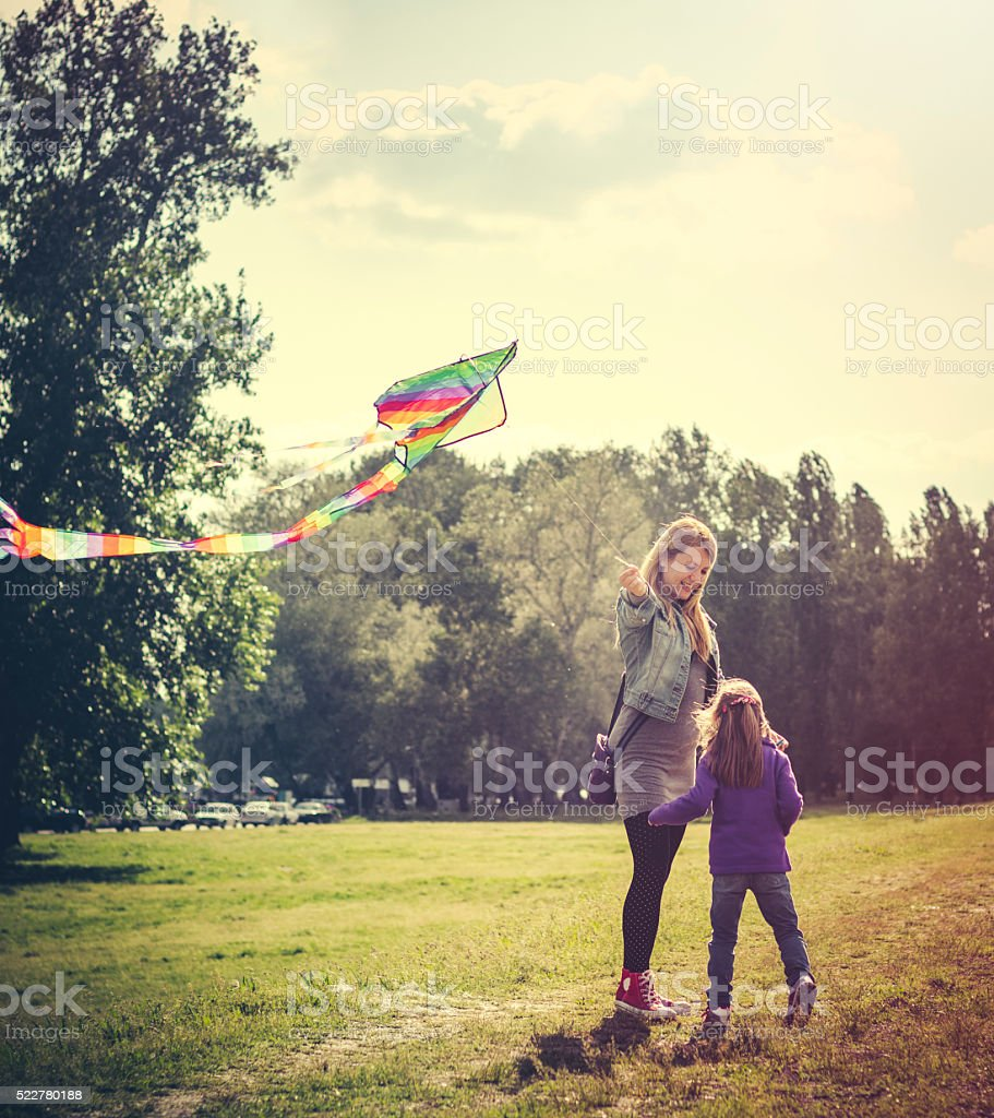 Mother and daughter flying kite outdoors stock photo
