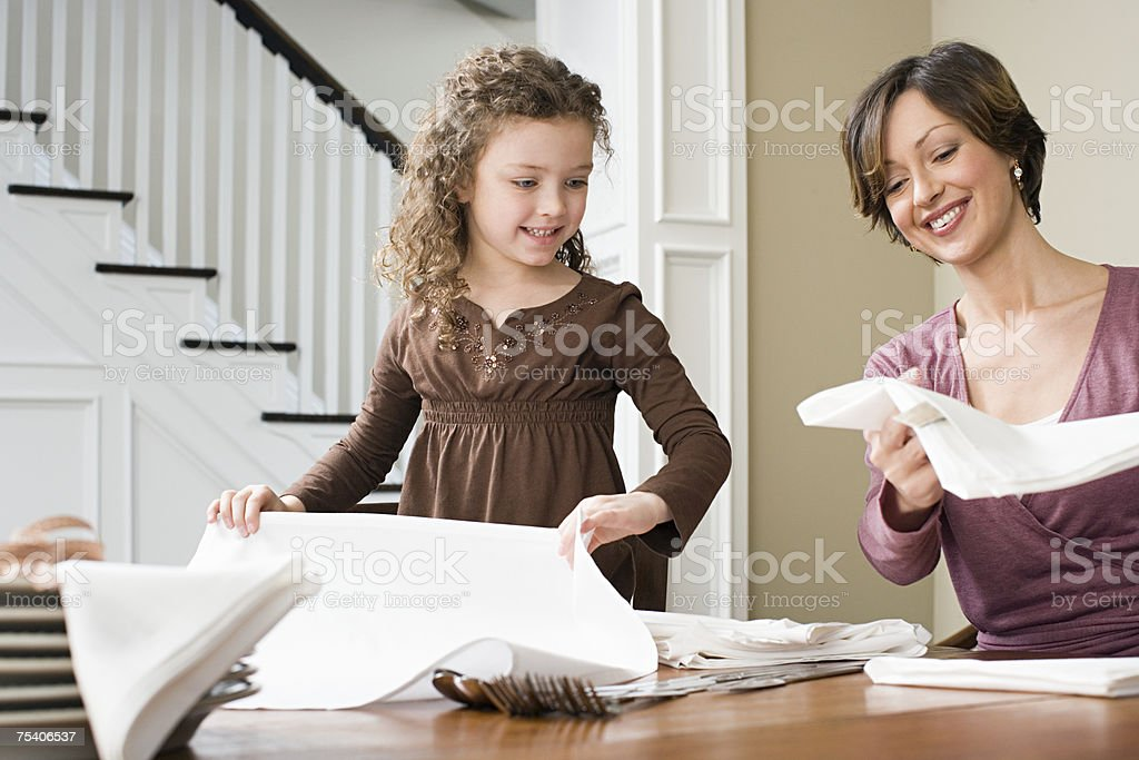 Mother and daughter folding napkins royalty-free stock photo