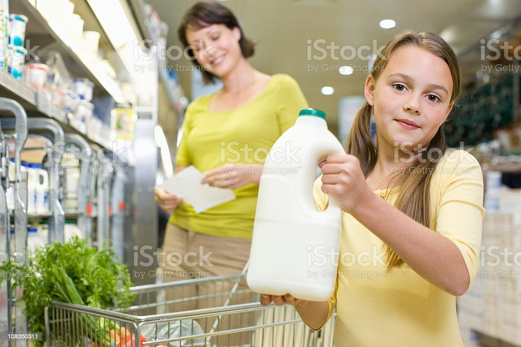 Mother and daughter getting milk in supermarket stock photo