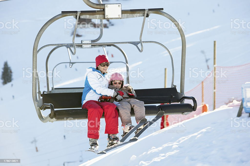 Mother And Daughter Getting Off chair Lift On Ski Holiday stock photo