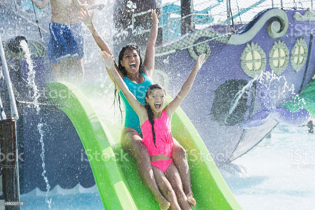 Mother and daughter going down water slide stock photo