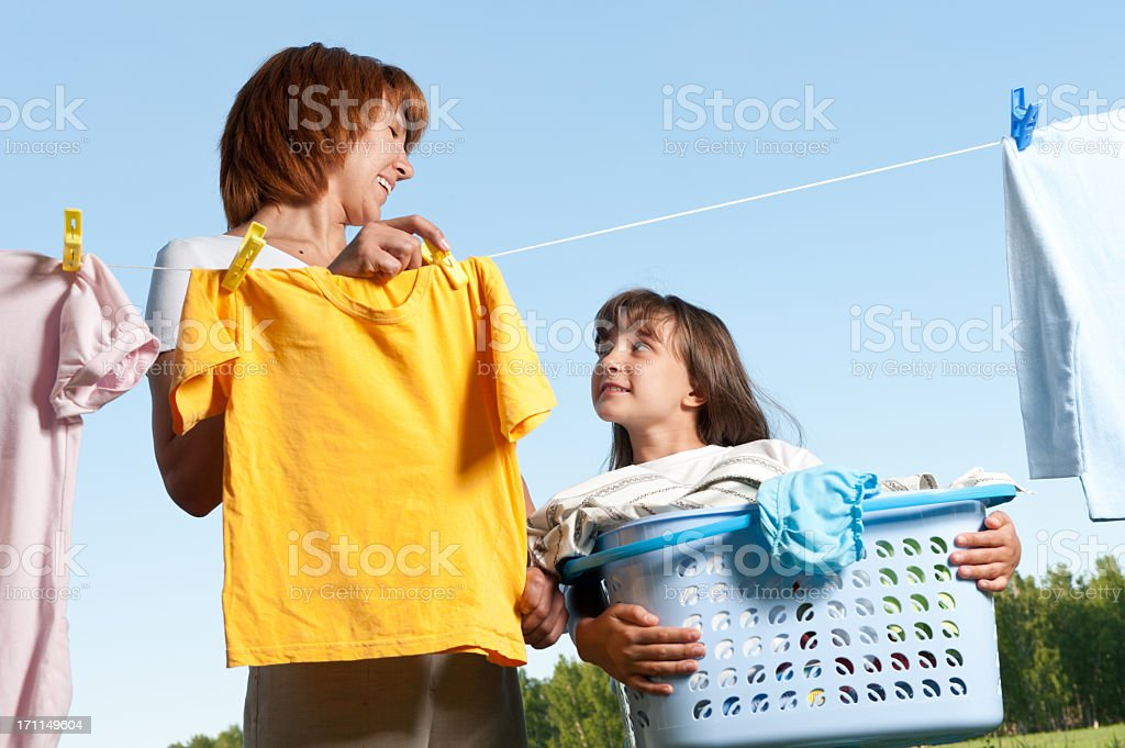 A mother and daughter handing laundry from a clothesline stock photo