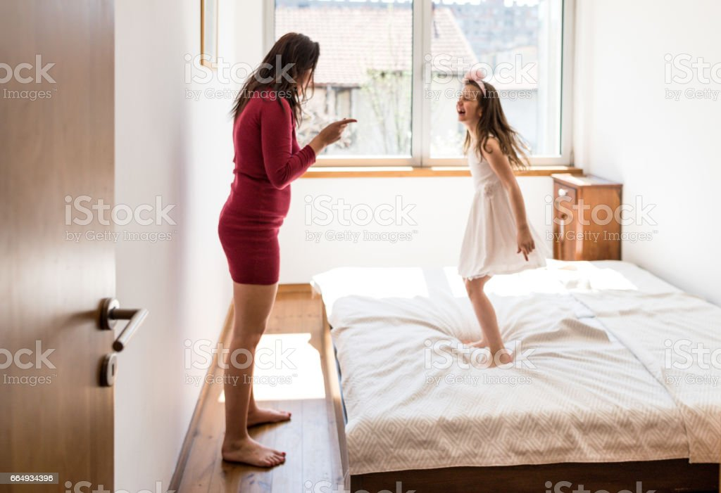 mother and daughter have fun in the bed stock photo