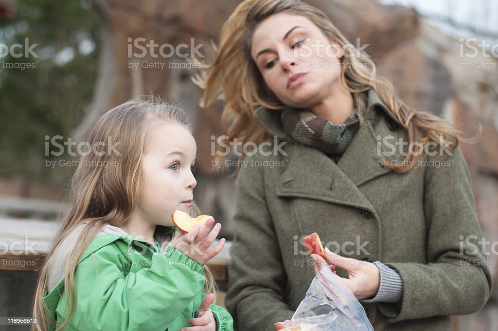 Mother and daughter having a snack outside stock photo