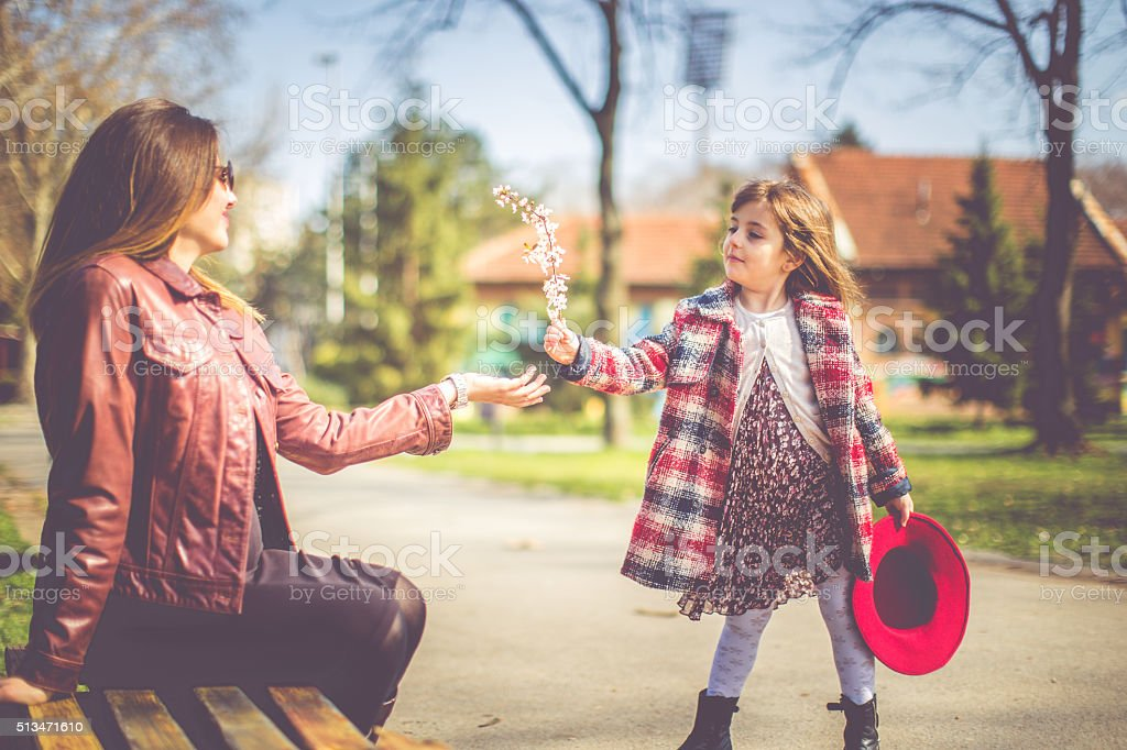 Mother and daughter having fun in autumn park stock photo