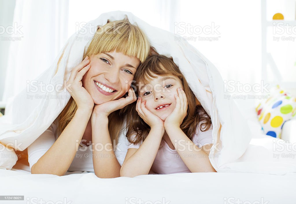 Mother and daughter having fun in bed. royalty-free stock photo