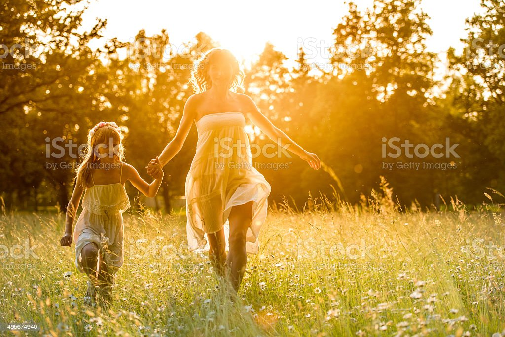 Mother and daughter having fun in forest at sunset stock photo
