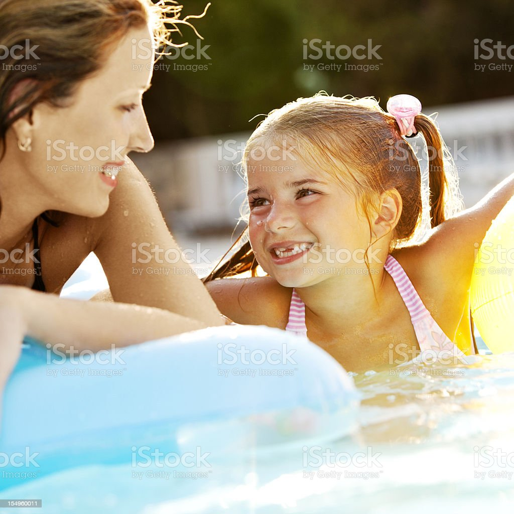 Mother and daughter having fun in pool royalty-free stock photo