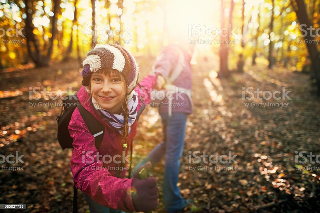 Mother and daughter having fun in the autumn forest stock photo