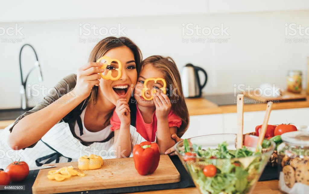 Mother and daughter having fun in the kitchen stock photo