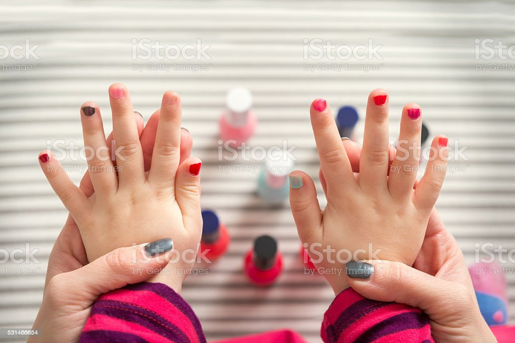 Mother and daughter having fun painting fingernails stock photo