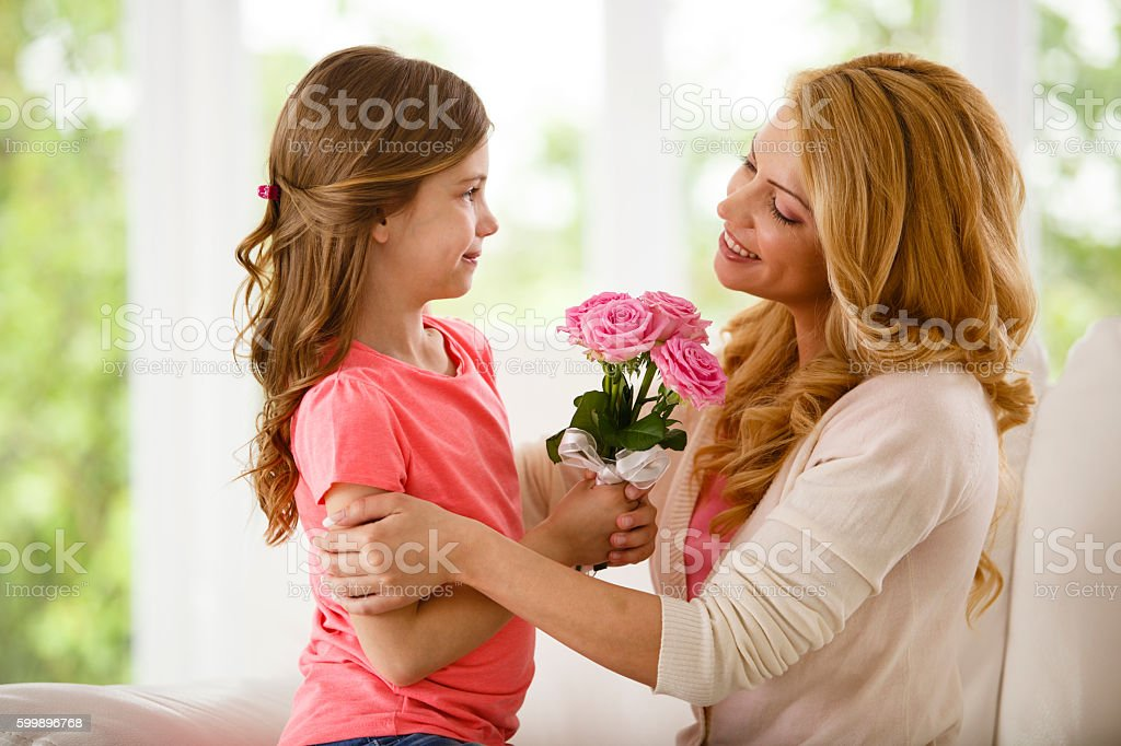 Mother and daughter holding bouquet of flowers stock photo