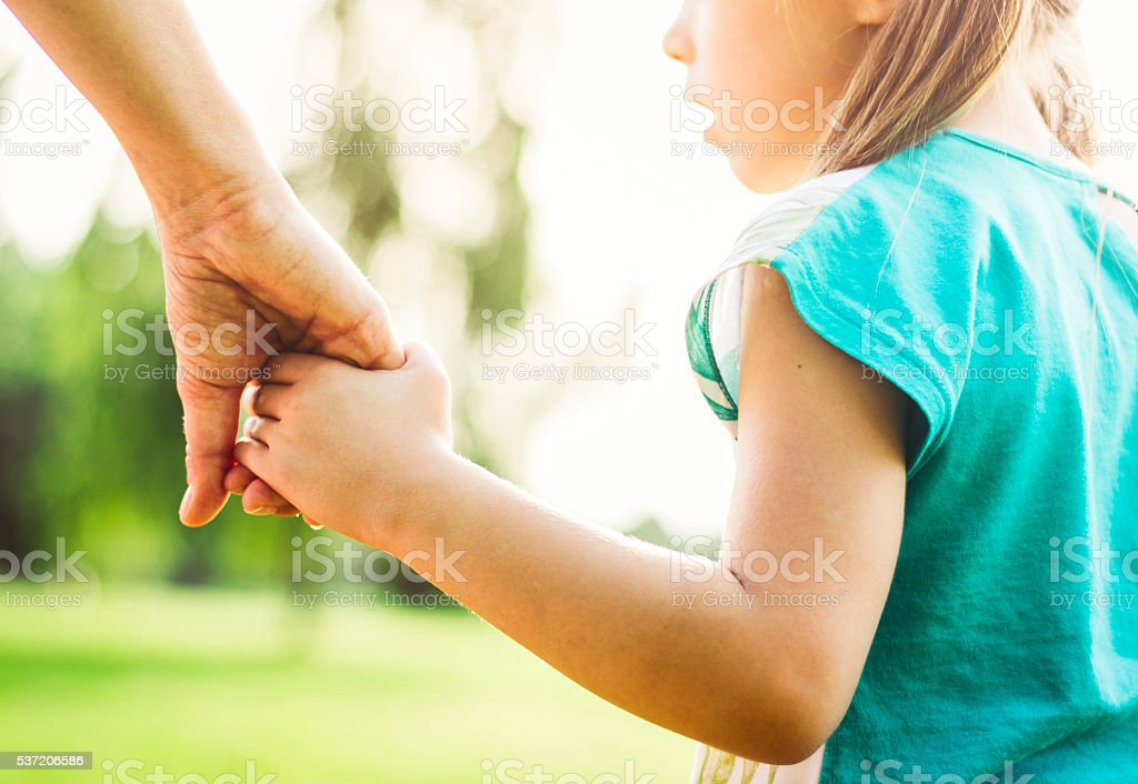Mother and daughter holding hands and walking stock photo