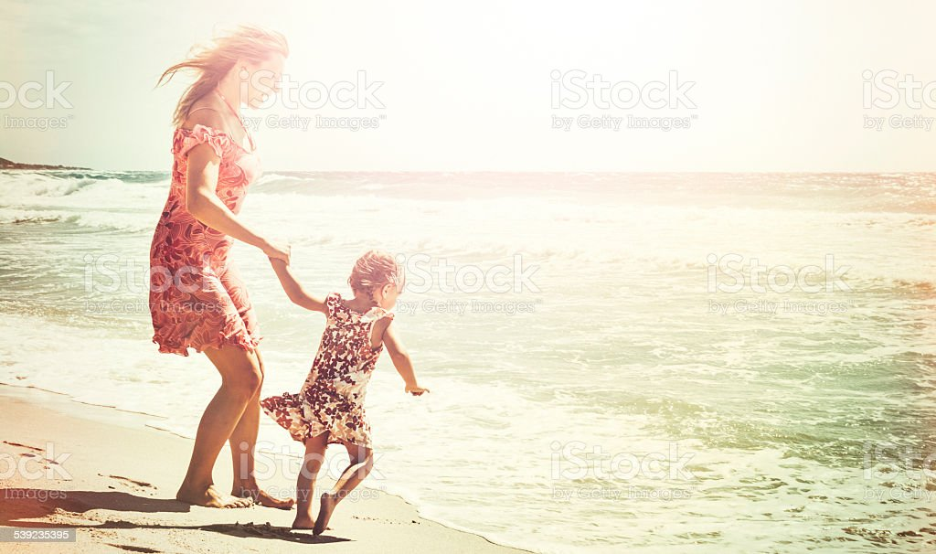 Mother and daughter holding hands at waves stock photo