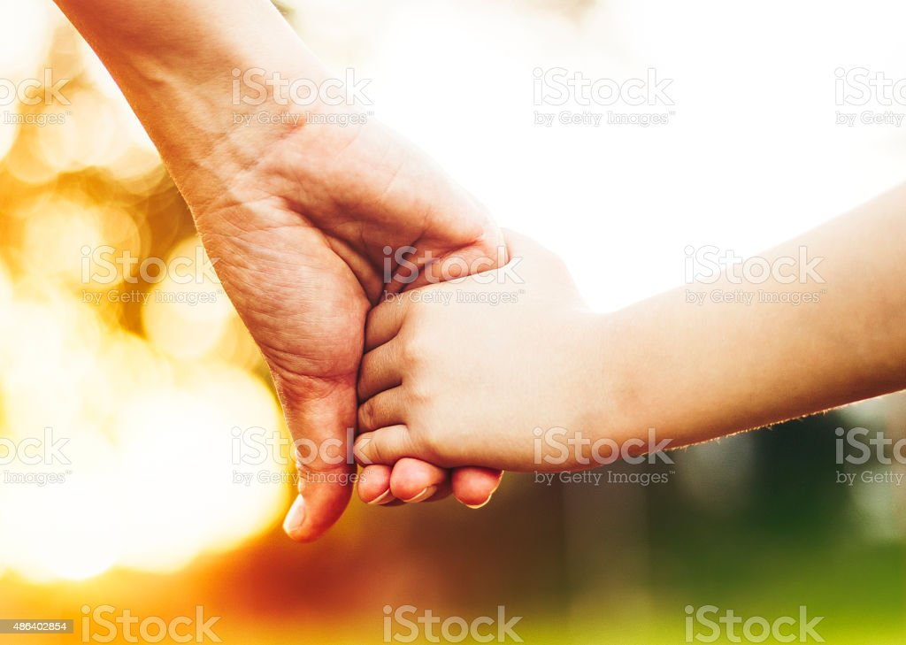 Mother and daughter holding hands closeup stock photo